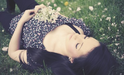 girl laying in flowers and grass