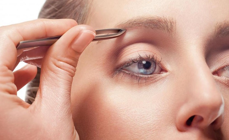 woman with blue eyes tweezing her eyebrows