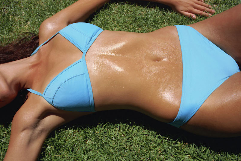 woman laying on grass in blue bikini