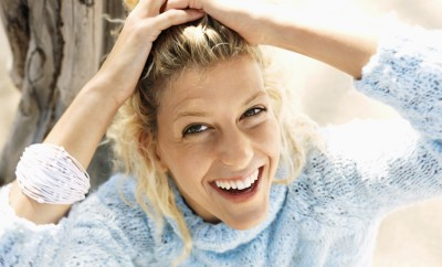 Smiling young blonde woman in blue sweater