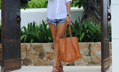leather weekend getaway bag on woman in jean shorts and white tee