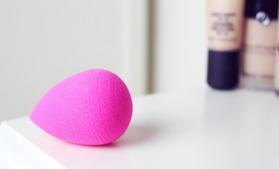 pink beautyblender on white counter with foundation