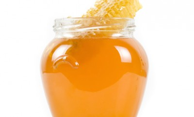 jar of organic honey on white background