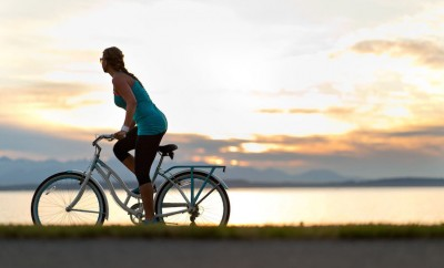 woman biking at sunset