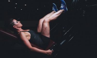 girl doing leg press in dark gym