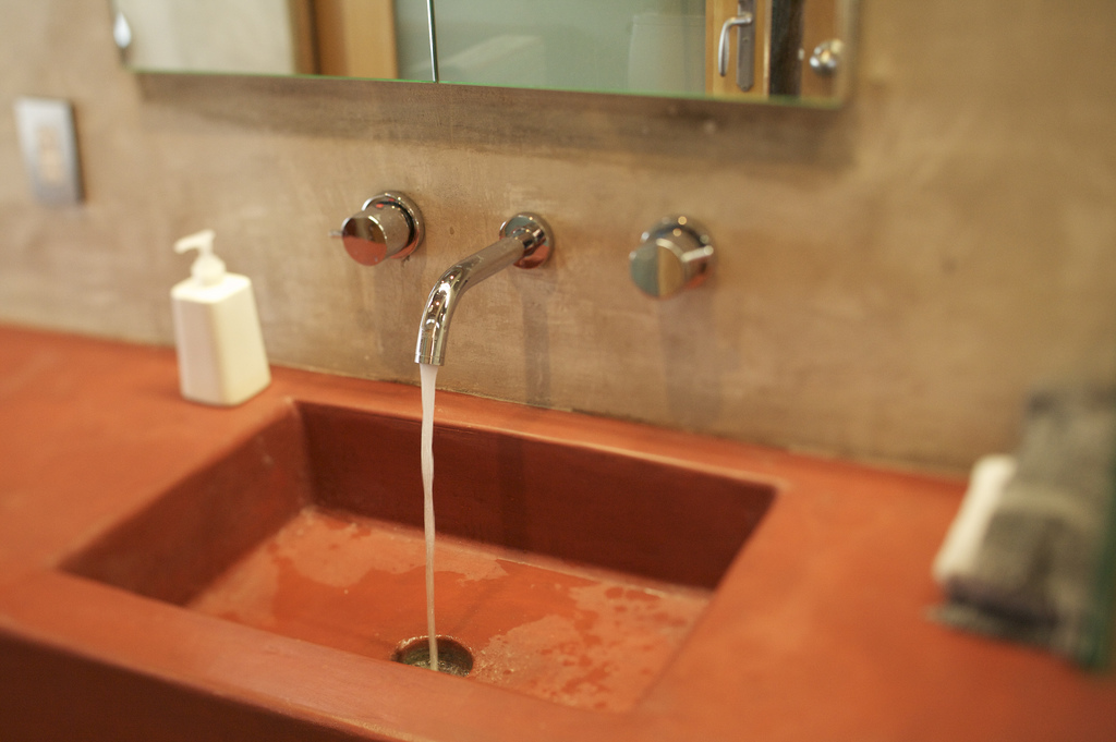 red sink with running faucet