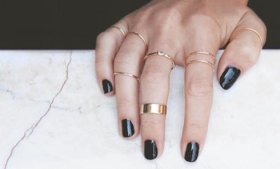 gold stacked rings on hand with black nail polish
