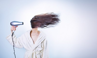 brunette woman blow drying her hair with blue background