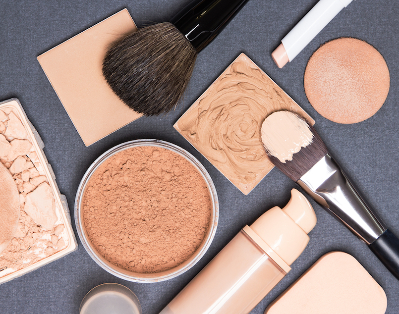 Close-up of concealer pencil corrector open liquid foundation bottle and jar of loose powder crushed compact powder makeup brushes and cosmetic sponges on gray textured surface