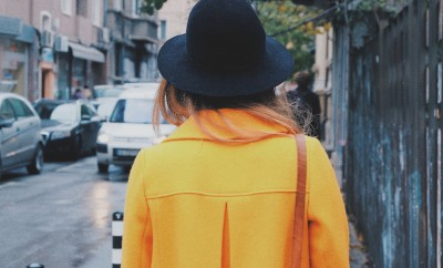 girl in yellow coat and black floppy hat in city