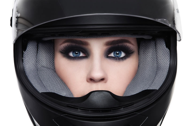 Close-up portrait of young beautiful woman in biker helmet over white background