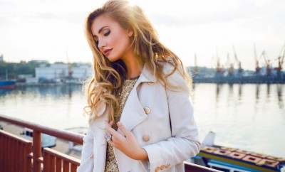 Fashion portrait of sensual sexy woman with perfect elegant hairstyle and natural makeup posing at sea port on sunset, wearing trendy light cashmere coat and golden top, Soft natural colors.