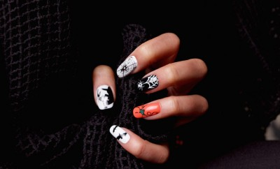 Halloween nails on woman holding black sweater