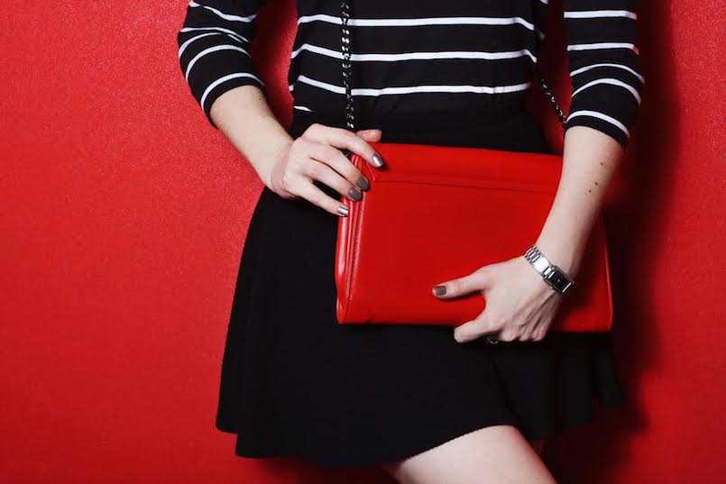 red crossbody bag on girl with black skirt and striped shirt