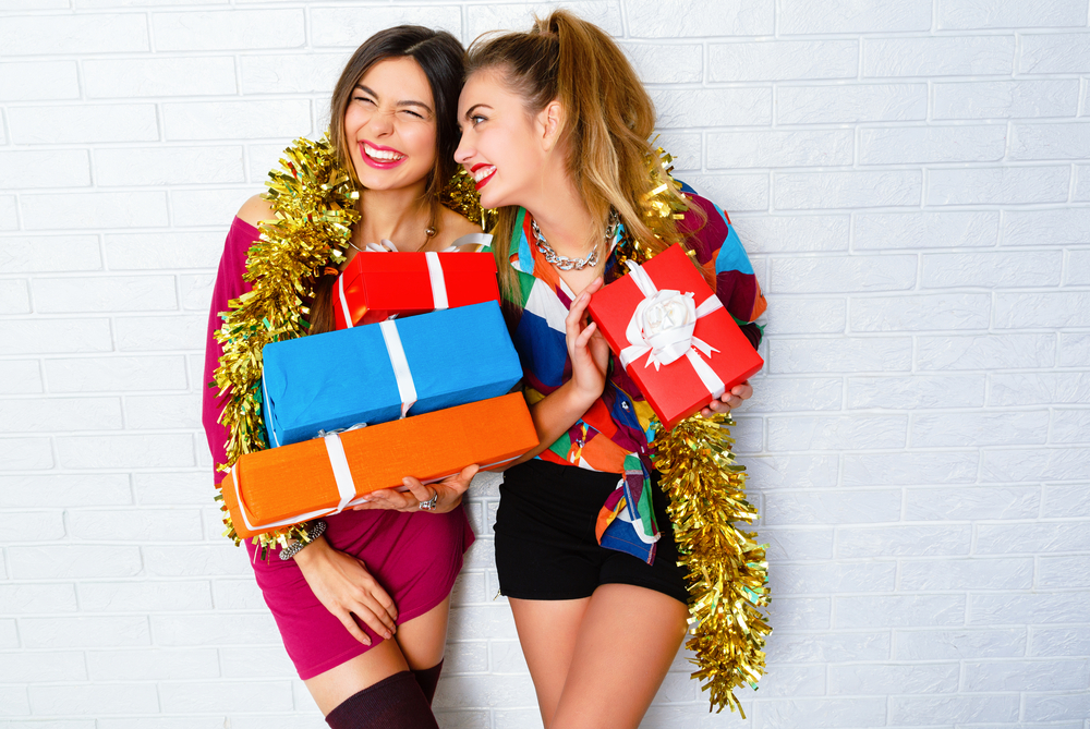 Fashion lifestyle portrait of two girls friends holding birthday bright presents, wearing trendy clothes and sparkled tinsel. Going crazy, and making funny faces