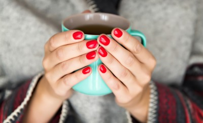 female hands holding a mug of hot tea