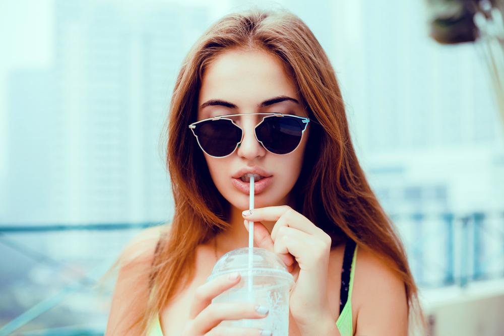 young beautiful happy stylish hipster girl,cocktail,smoozy drink,cold juice,smile and laughing,fashionable sunglasses,cool accessories, purse,amazed, vintage style,street background, hair, wind