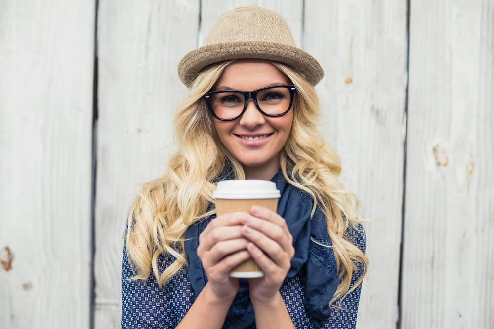 Cheerful fashionable blonde holding coffee outdoors on wooden background