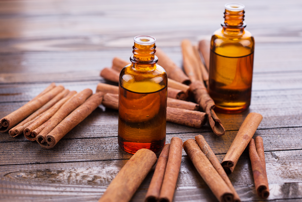 Essential aroma oil with cinnamon on wooden background