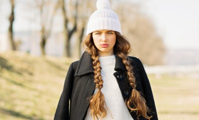 Portrait of gorgeous teenage girl with long blonde braided hair in winter outfit. Beautiful young woman with braids wearing black coat, white sweater and knitted white hat