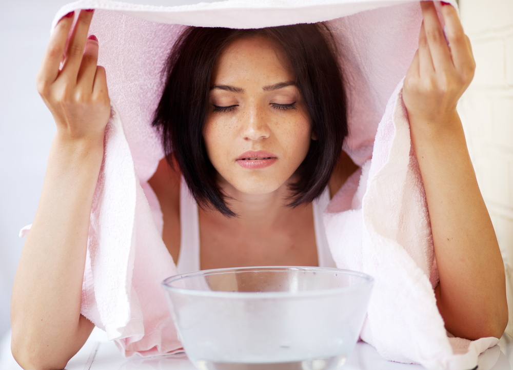 Relaxing during a facial steam treatment at a beauty spa