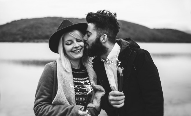 Young couple having fun and celebrating life, holding sprinkles and kissing