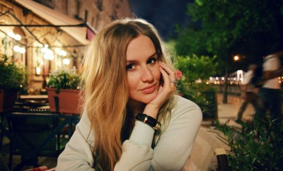 Young pretty blonde woman sitting at cafe in evening time