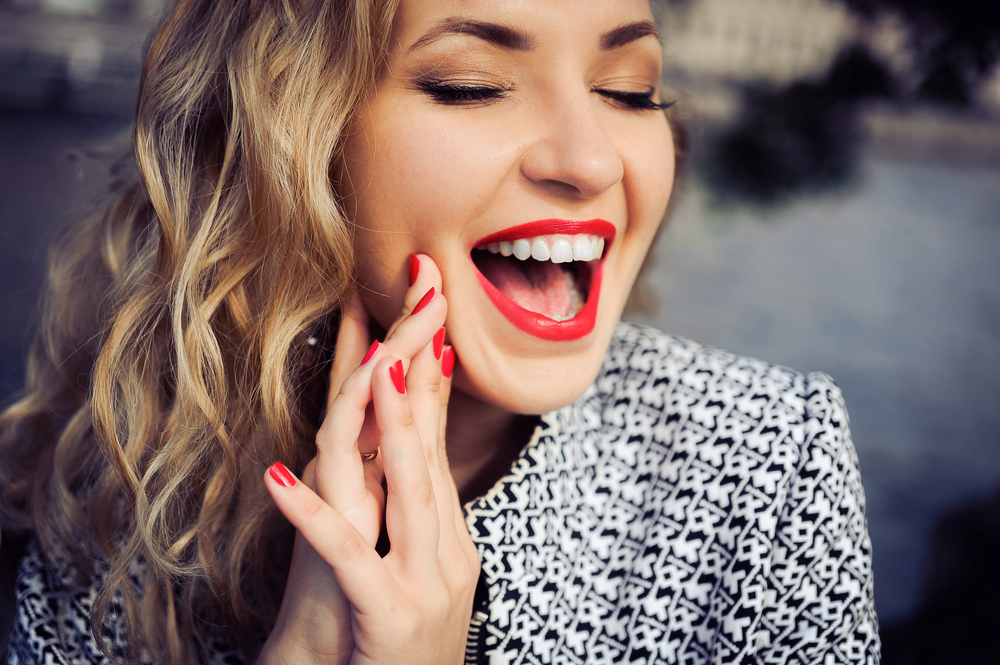 close-up portrait of a young girl hipster beautiful blonde in sunglasses with red lips laughing and posing against the backdrop of the city