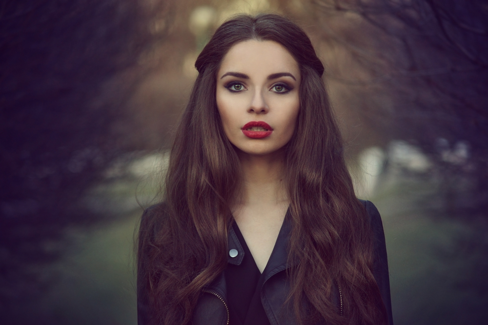 Art portrait of beautiful lonely girl. Pretty woman with long dark hair and red lips posing in forest and looking at you. Shallow DOF
