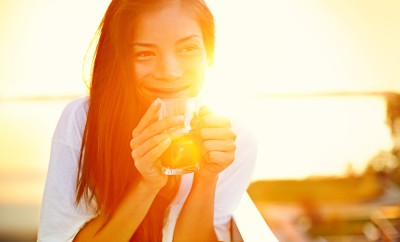 Asian woman drinking coffee in sun sitting outdoor in sunshine light enjoying her morning coffee. Smiling happy multiracial female Asian Chinese