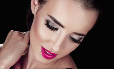 Beauty Woman with Perfect Makeup. Beautiful Professional Holiday Make-up. Red Pink Lips and Nails. Beauty Girl's Face isolated on Black background