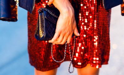 Close-up image of bright party woman's clothes,stylish hipster girl,denim jacket,jewelry, fashion,teen,cool accessories,purse, hat, sunglasses,amazed,vintage style,urban city background,black handbag