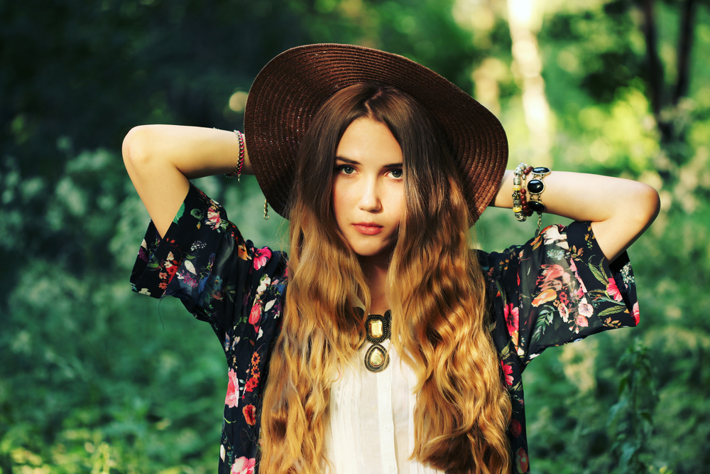 Fashion portrait of beautiful hippie young woman wearing boho chic clothes and summer hat outdoors. Soft warm vintage color tone. Artsy bohemian style