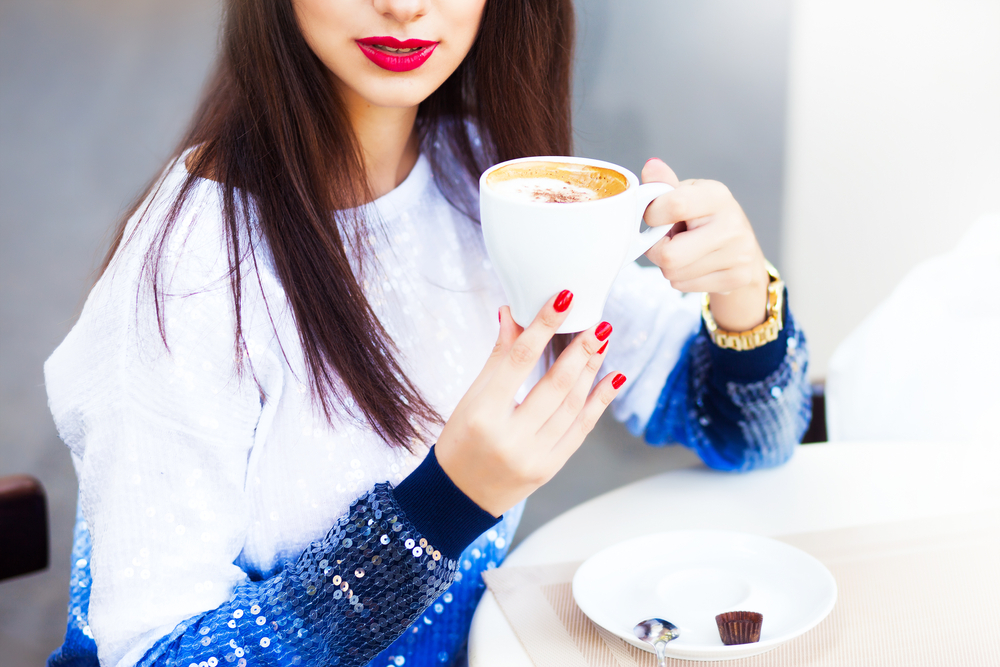 Lifestyle soft image of girl holding white cup of coffee at street cafe,white stylish outfit,cup to table,amazing red nails,red lips,toned,enjoy time.Instagram filters,enjoy time,gold accessories,hand