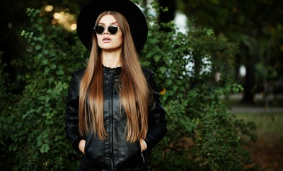 Street fashion concept - pretty young slim woman in rock black style, wearing stylish sunglasses and black leather jacket. Young cheerful fashion woman