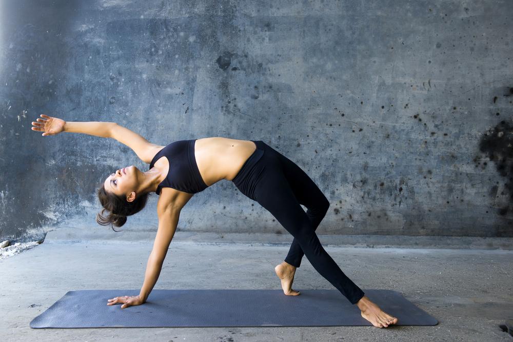 Woman practicing advanced yoga against a dark texturized wall