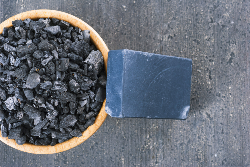 block of natural carbon soap and a pile of coal on black wood table background