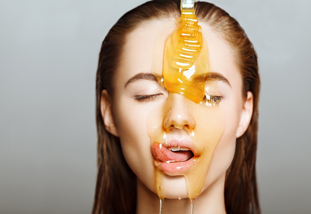 Beautiful woman with honey on her face. Healthy perfect skin. Honey treatment