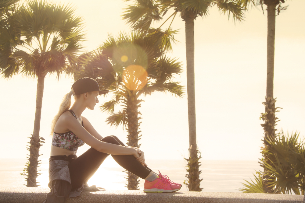 Beautiful young woman relaxing close to the sea after the hard workout and watching sunset. Golden colors made nice feeling and matching with long blonde hair of the girl