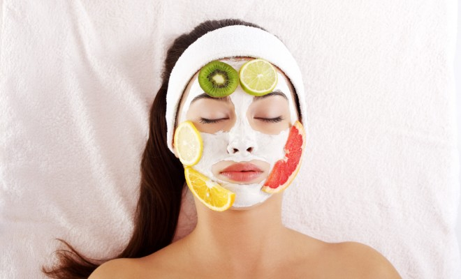 Beautiful young woman with fruit mask on a face
