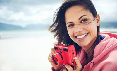 Portrait of beautiful Latino woman with retro hipster camera having fun at the beach
