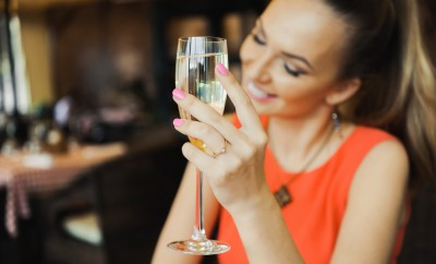 close-up portrait of a beautiful young elegant sexy blonde woman in the cafe with a glass of champagne,White wine smiling and drink posing, with a ring on her finger, she is engaged
