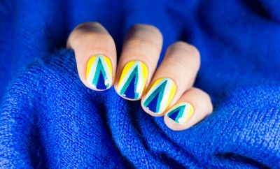 Beautiful manicure. Nail polish being applied to hand, polish is a blue color. Blue background closeup