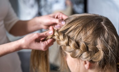 Hairdresser make braid in beauty salon