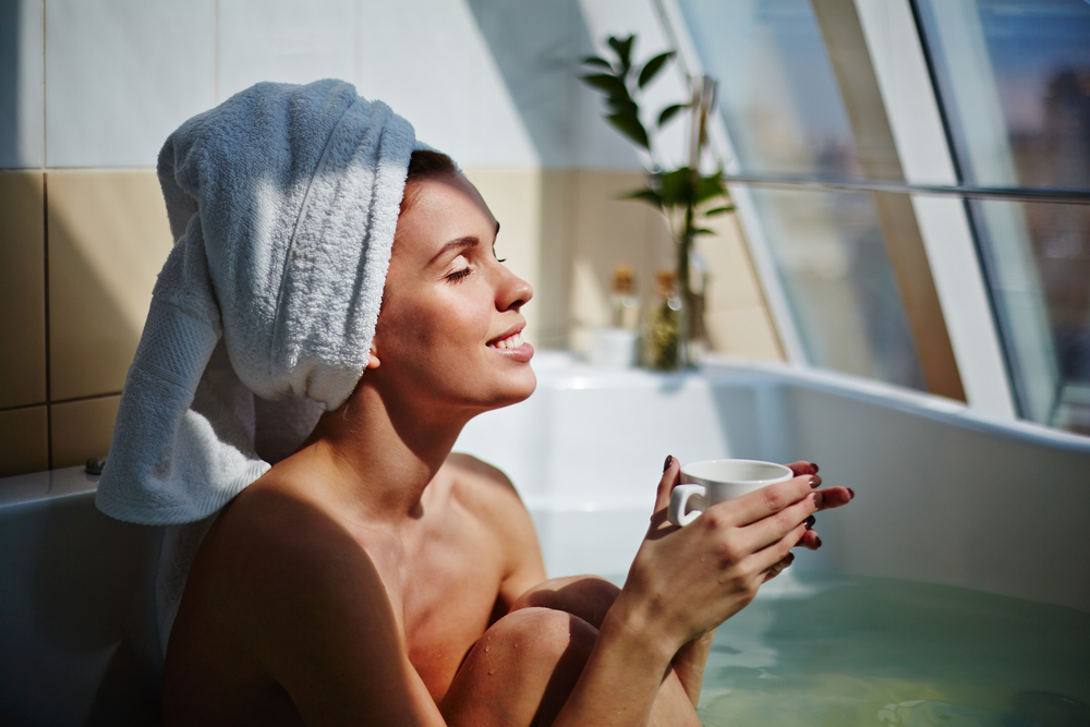 Relaxed girl sitting in bath with cup of herbal tea