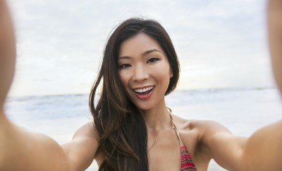 Asian young woman or girl in bikini, taking vacation selfie photograph at the beach