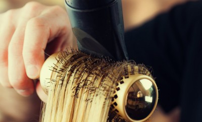Drying blond hair with hair dryer and round brush