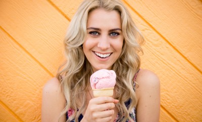 A cute twenty something woman has fun while eating her strawberry ice cream cone while standing in front of an wooden bright orange wall
