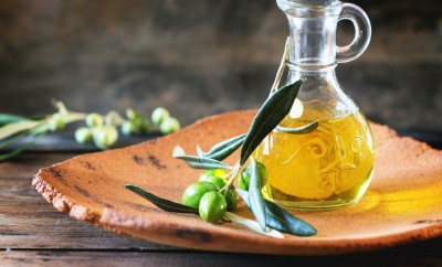 Battle of olive oil with olive branch in handmade clay plate over wooden table.
