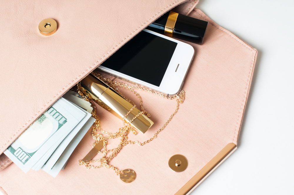Cosmetics, jewelry, money and smartphone in an open beige woman's clutch handbag on a white background